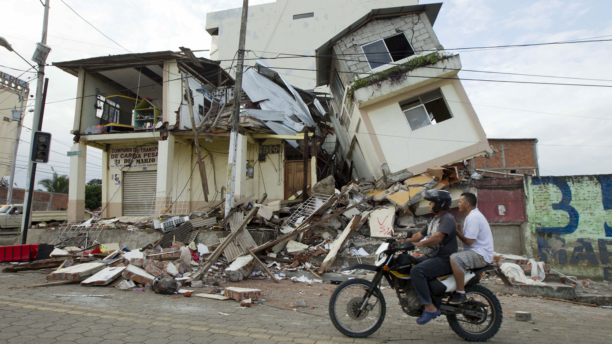 Men ride a motorcycle past damaged buildings in Pedernales, after an earthquake struck off Ecuador's Pacific coast, April 18, 2016. REUTERS/Guillermo Granja TPX IMAGES OF THE DAY      - RTX2AIOR