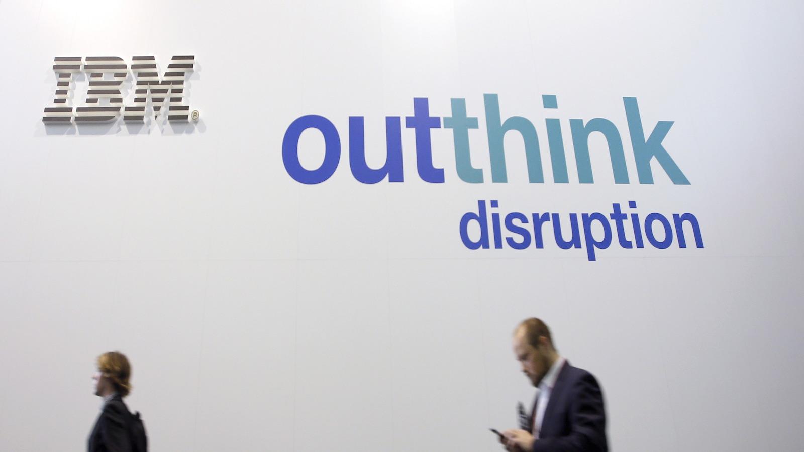 People walk past an IBM logo during