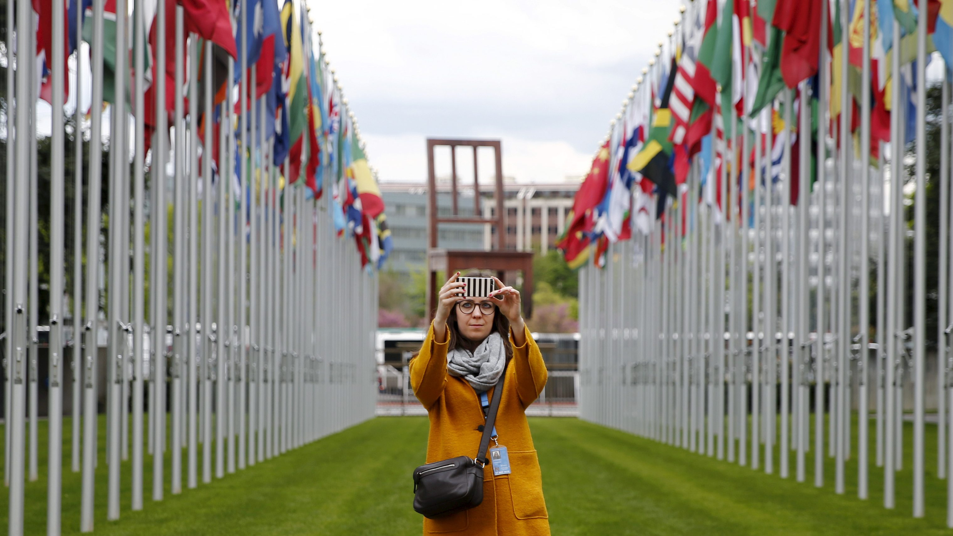 A staff takes a selfie in the flags alley at the European headquarters of the United Nations in Geneva, Switzerland, April 26, 2016.   - RTX2BP9D