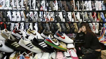 A shopkeeper selling counterfeit shoes waits for customers at stall in Beijing.