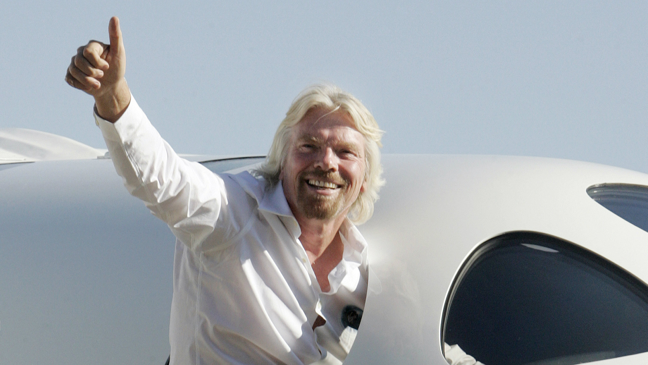 Virgin Group's Founder billionaire Richard Branson waves from the window of Virgin Galactic's mothership WhiteKnightTwo during its public roll-out in Mojave, California July 28, 2008