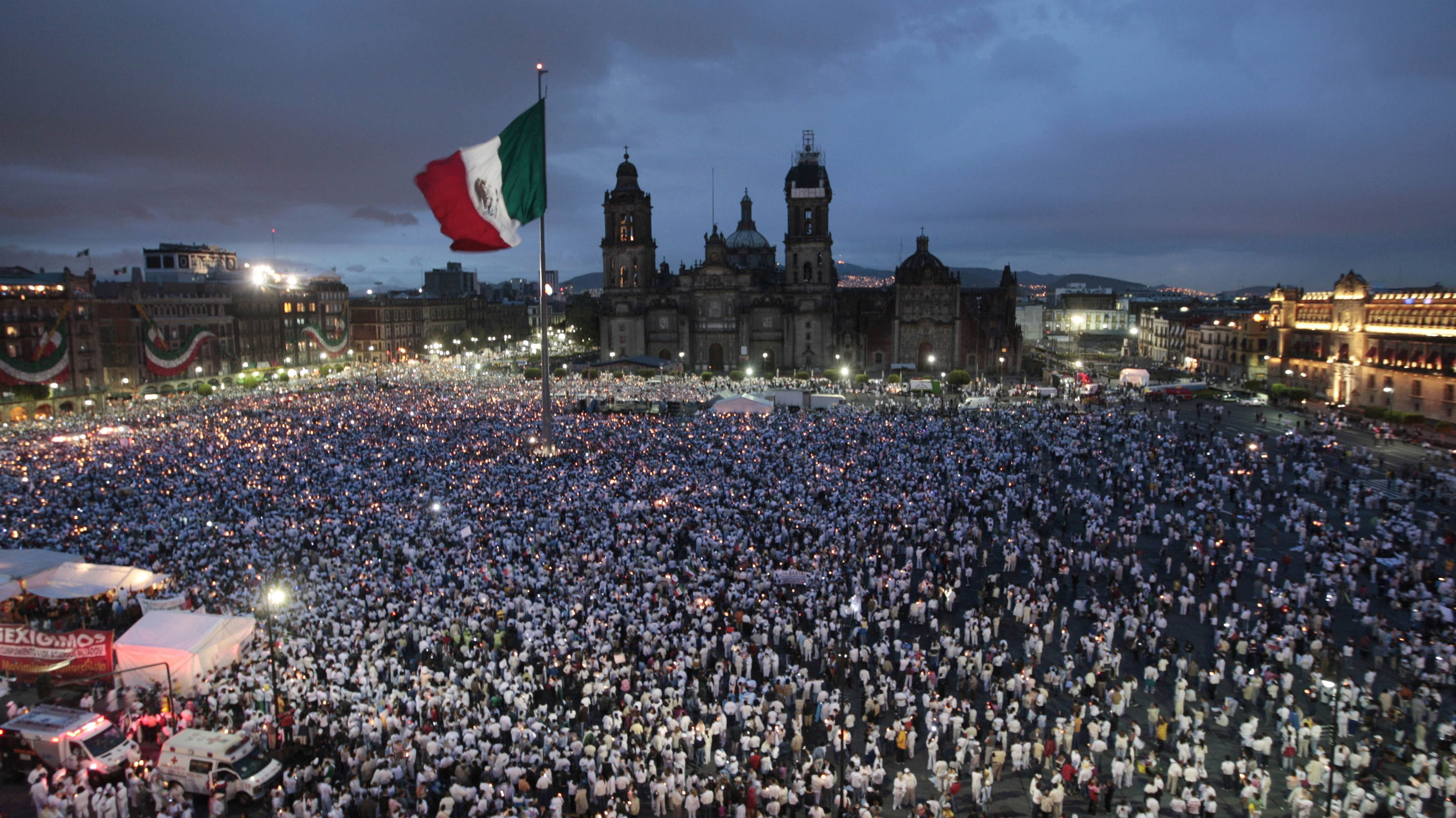 People hold candles at Zocalo square in Mexico City