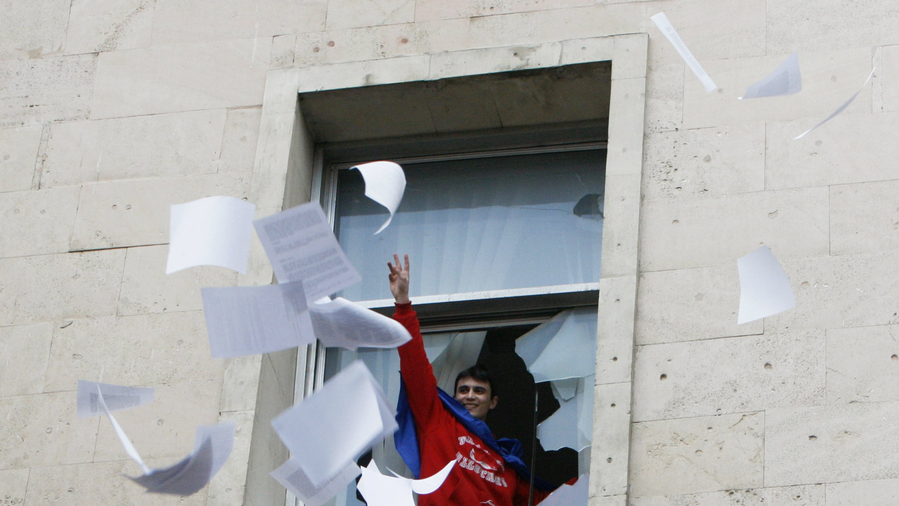 A man throws documents out of a window of the parliament building in Chisinau April 7, 2009. Protesters denouncing a Communist election victory in Moldova siezed the president's offices on Tuesday and broke into parliament where they hurled furniture and computers into the street, Reuters reporters said. REUTERS/Gleb Garanich