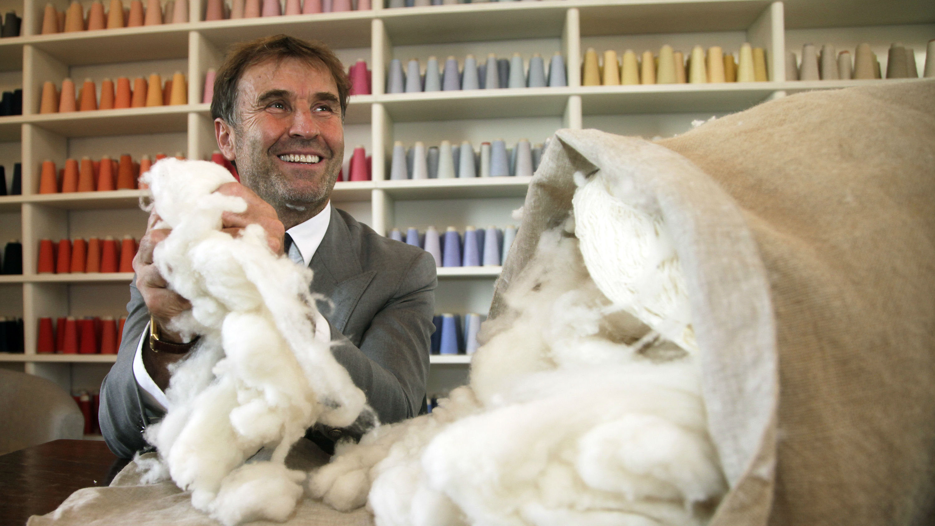 Italian clothing designer Brunello Cucinelli holds raw cashmere wool in the Umbrian village of Solomeo October 7, 2009. He has been called the King of Cashmere, an entrepreneur with the mind of a capitalist but the heart of a philosopher, the Don Qixote of Italy's luxury fashion world, an idealist madman. Brunello Cucinelli is anything but an orthodox businessman. But the double-digit revenue and profit growth his luxury fashion label has produced in the past three years would make any company turn asparagus green - one of his shades - with envy. Picture taken October 7, 2009. REUTERS/Alessandro Bianchi (ITALY)