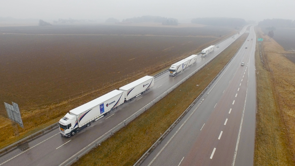 Three Scania trucks in a column formation on a highway