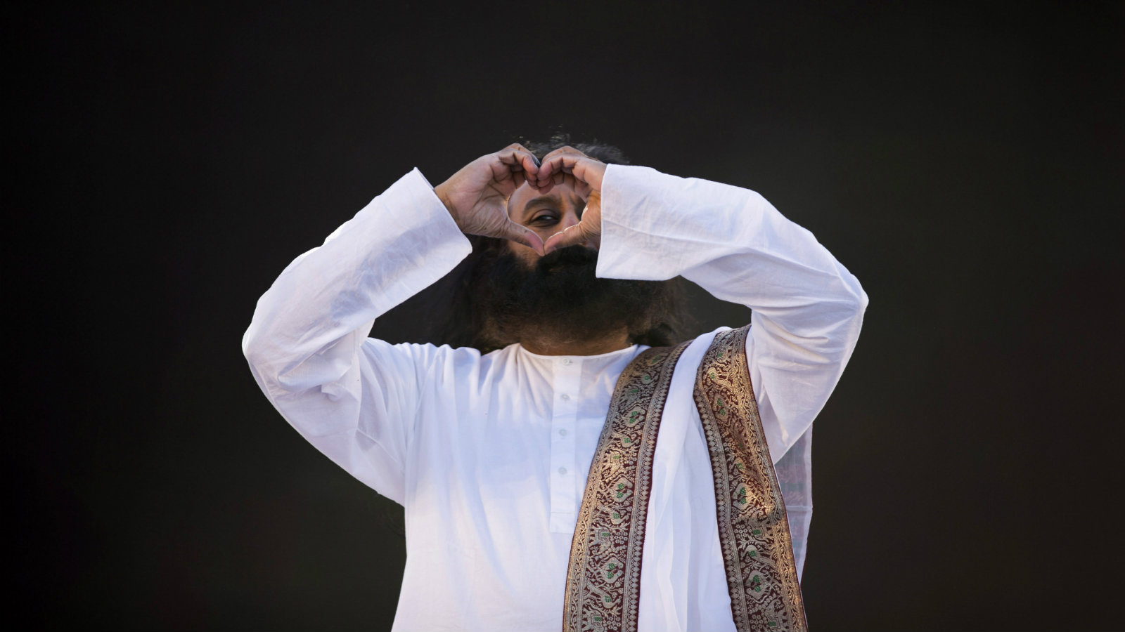 India's spiritual leader and founder of Art of Living Foundation Sri Sri Ravi Shankar looks to the crowd through a heart formed with his hands before leading a meditation with thousands of participants in Buenos Aires, Argentina, Sunday, Sept. 9, 2012.