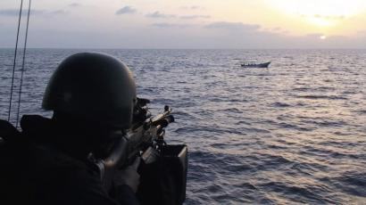 A soldier aboard a Swedish vessels lines up a suspected pirate vessel, 2009.