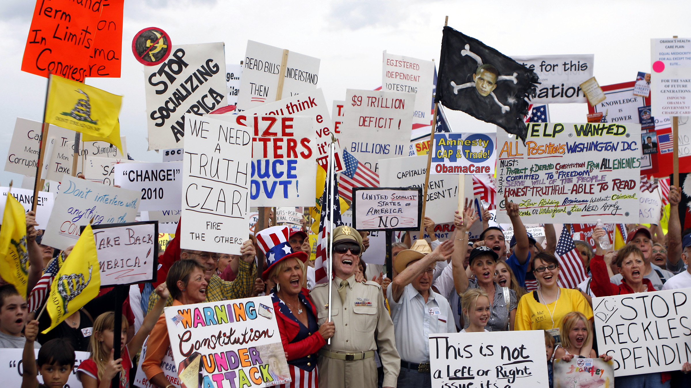 """People hold signs during a """"tea party"""" protest in Flagstaff, Arizona August 31, 2009. Organizers say the event is an effort to work against members of Congress who voted for higher spending and taxes."""