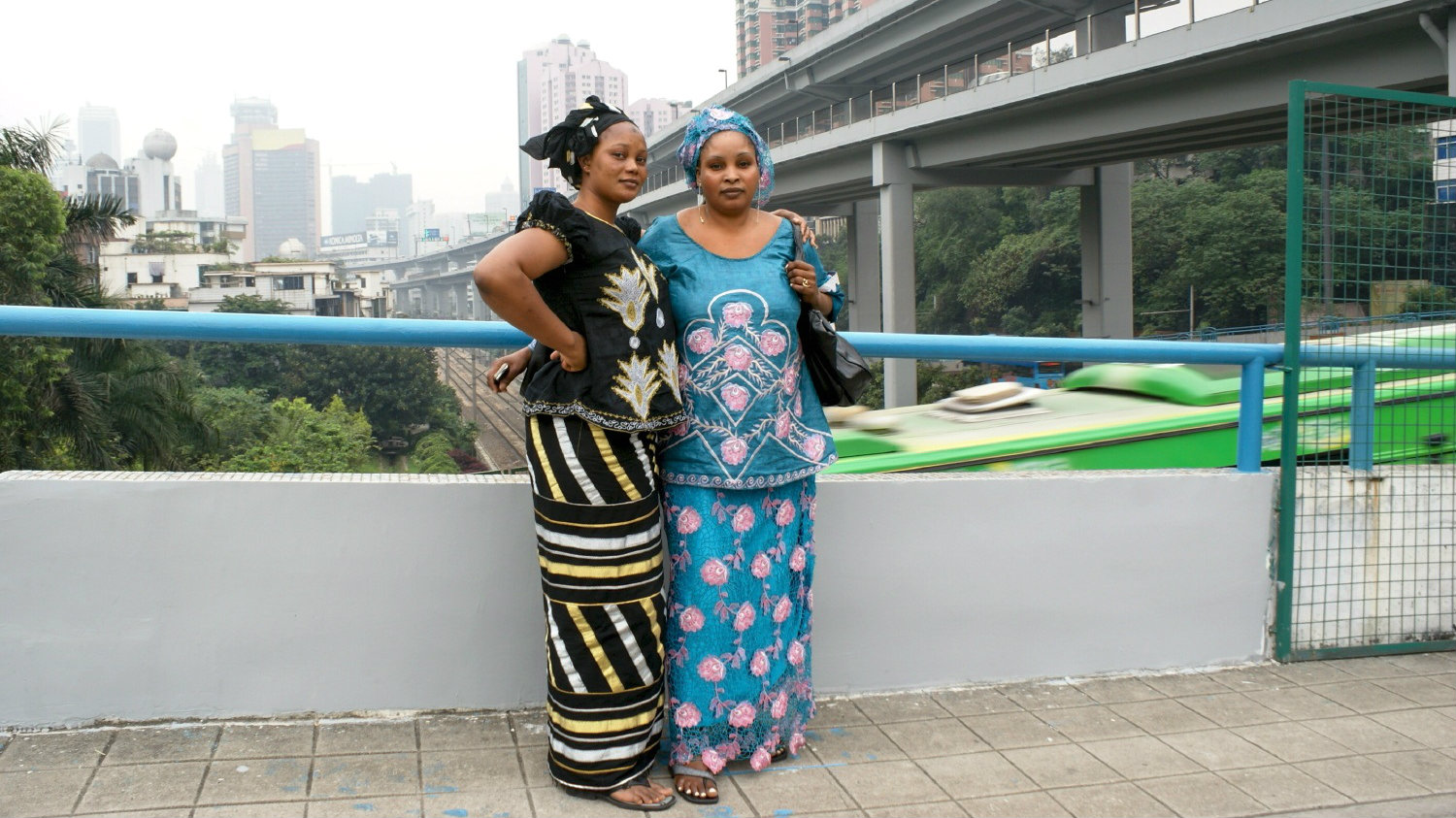 Two women pose for their portrait on a bridge in Guangzhou.