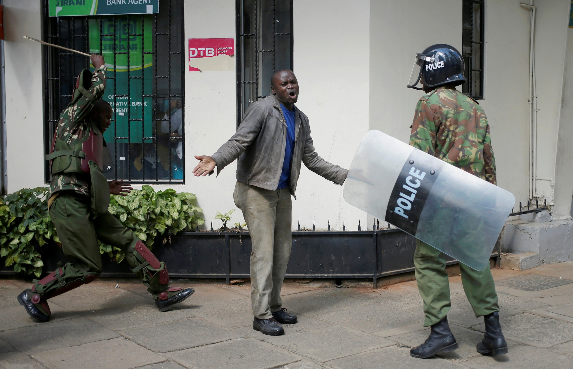 Kenyan policemen beat a protester during clashes in Nairobi on May 16th.