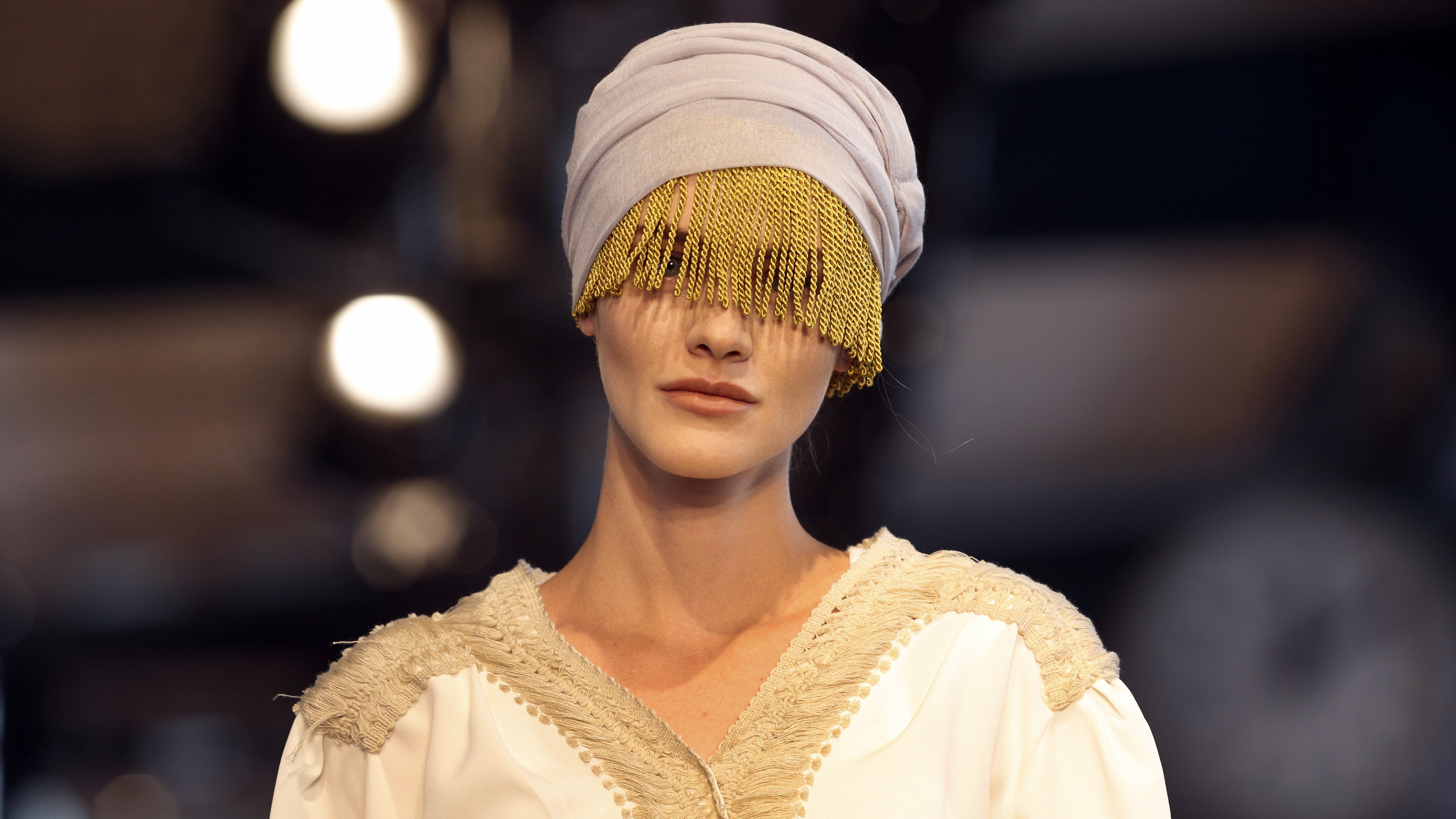 A model hits the runway of a fashion show during the International Modest Fashion Week, in Istanbul, Friday, May, 13, 2016. Turkey's first International Modest Fashion Week has opened in Istanbul bringing designers and models of conservative wear from around the world. The two-day event kicked off Friday with models hitting the runway at a historic train station donning a bright palette of breezy garment and kaleidoscopic headscarves. (AP Photo/Lefteris Pitarakis)