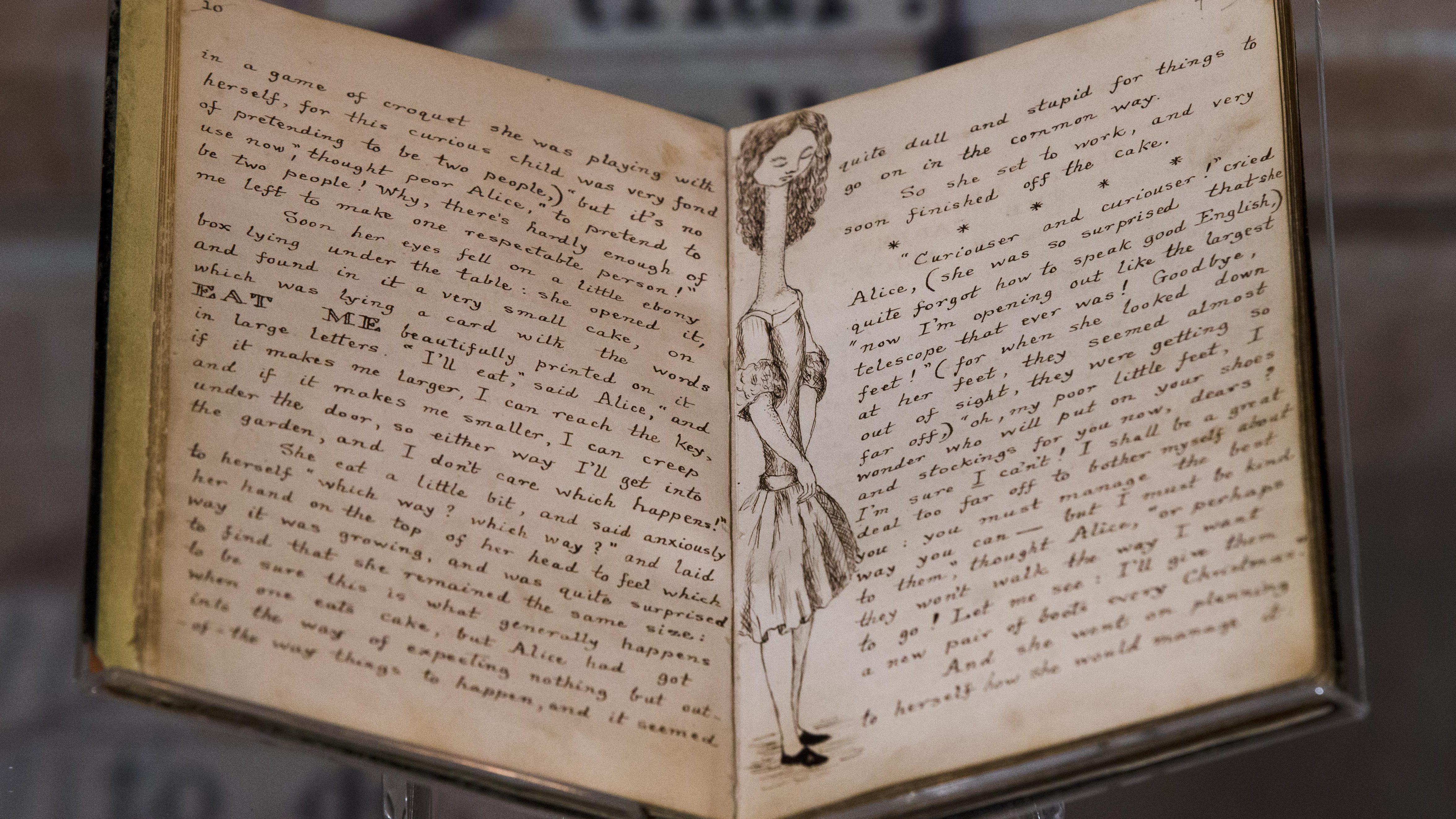 The illustrated original manuscript for Lewis Carroll's Alice's Adventures in Wonderland is displayed at the Rosenbach of the Free Library of Philadelphia Tuesday, Oct. 13, 2015, in Philadelphia. The manuscript is scheduled to be on display from Wednesday, Oct. 14 to Sunday, Oct. 18 to commemorate the 150th anniversary of the publication of Alice's Adventures in Wonderland. (AP Photo/Matt Rourke)