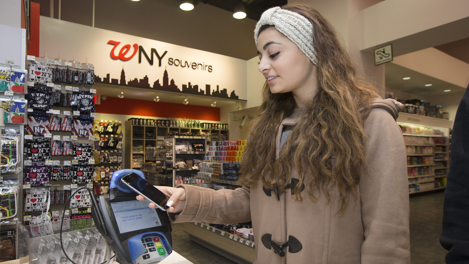 IMAGE DISTRIBUTED FOR MASTERCARD - A customer makes a purchase with a MasterCard using Apple Pay on the iPhone 6 at Walgreens in Times Square, Monday, Oct. 20, 2014, in New York. The service launched Monday.