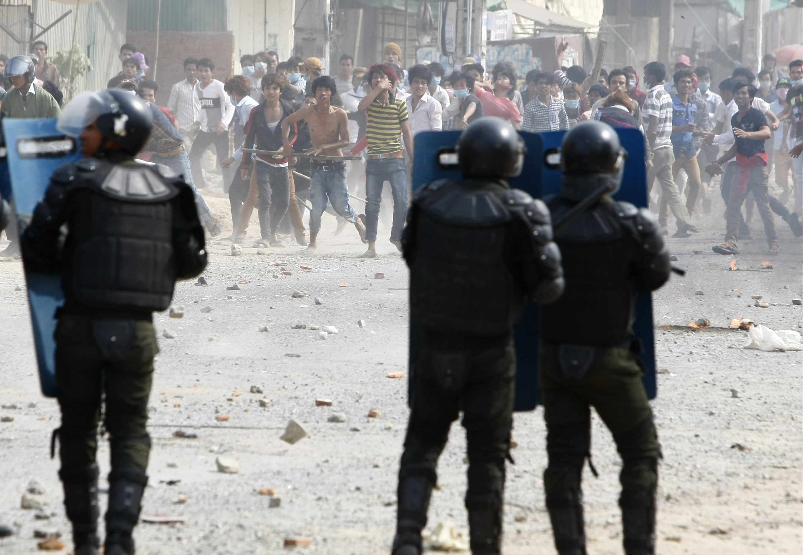 Cambodia garment workers throw stones at riot police during a strike near a factory on the Stung Meanchey complex on the outskirts of Phnom Penh, Cambodia, Friday, Jan. 3, 2014. At least three people were killed Friday when police in Cambodia opened fire to break up a protest by striking garment workers demanding a doubling of the minimum wage, police and human rights workers said.(AP Photo/Heng Sinith)