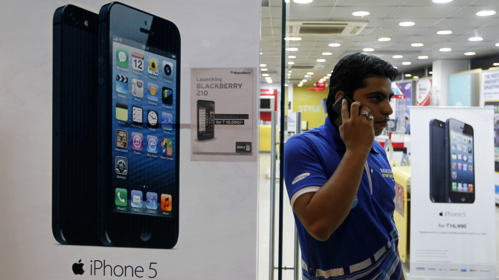 A man speaks on his mobile phone while standing next to posters advertising an Apple iPhone 5 and Blackberry Z10 in Ahmedabad February 22, 2013. More than four years after it started selling iPhones in India, Apple Inc is now aggressively pushing the iconic device through instalment payment plans that make it more affordable, a new distribution model and heavy marketing blitz. The result: iPhone shipments to India between October and December of 2012 nearly tripled to 250,000 units from 90,000 in the previous quarter, according to an estimate by Jessica Kwee, a Singapore-based analyst at consultancy Canalys. Picture taken February 22, 2013