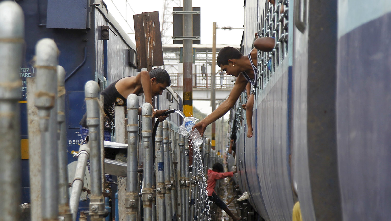 A passenger (R) fills water in a bottle from a pipe that supplies water to trains at a railway station on a hot summer day in Allahabad, India, June 11, 2015. Temperature in Allahabad on Thursday is expected to reach 44 degree Celsius (111.2 degree Fahrenheit), according to India's metrological department website.