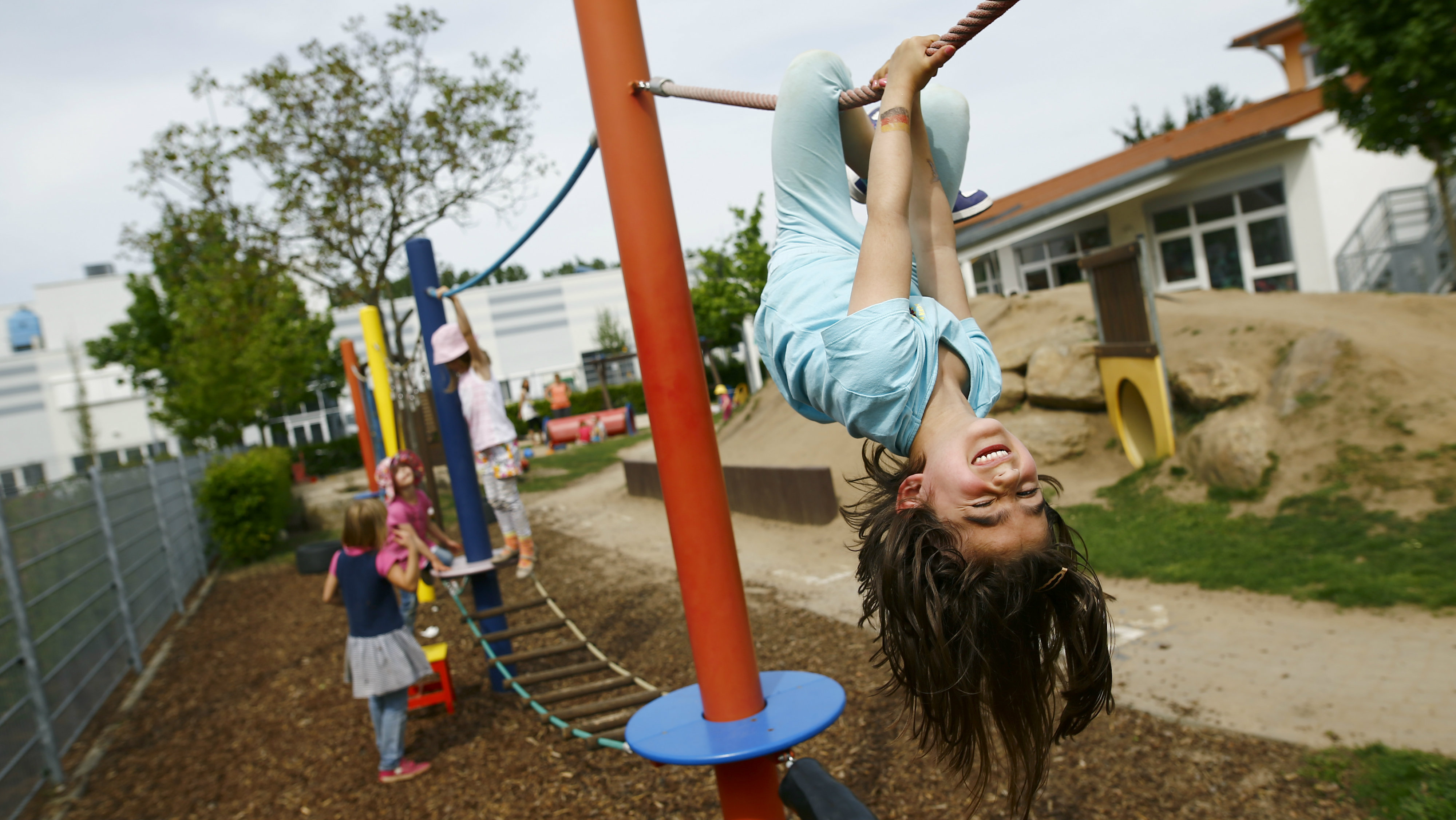 Children play in the garden of their kindergarten run by a private foundation which is not affected by the nursery caretakers' strike in Hanau, 30km south of Frankfurt, Germany, May 11, 2015. Most of the kindergartens run by public services all over Germany face a strike of the nursery caretakers as they fight for higher wages and better working conditions. REUTERS/Kai Pfaffenbach