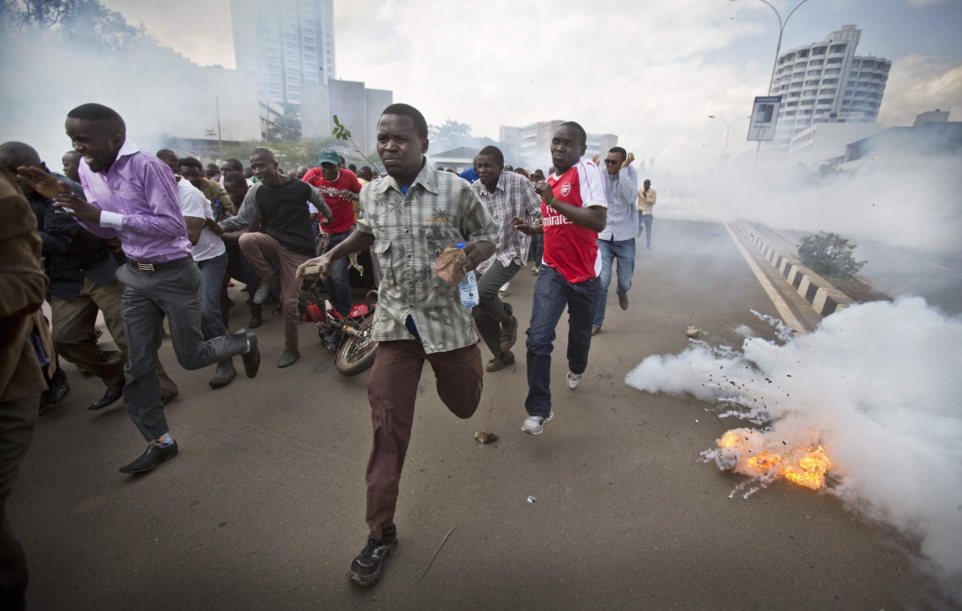 Opposition supporters, some carrying rocks, flee from exploding tear gas grenades fired by riot police.
