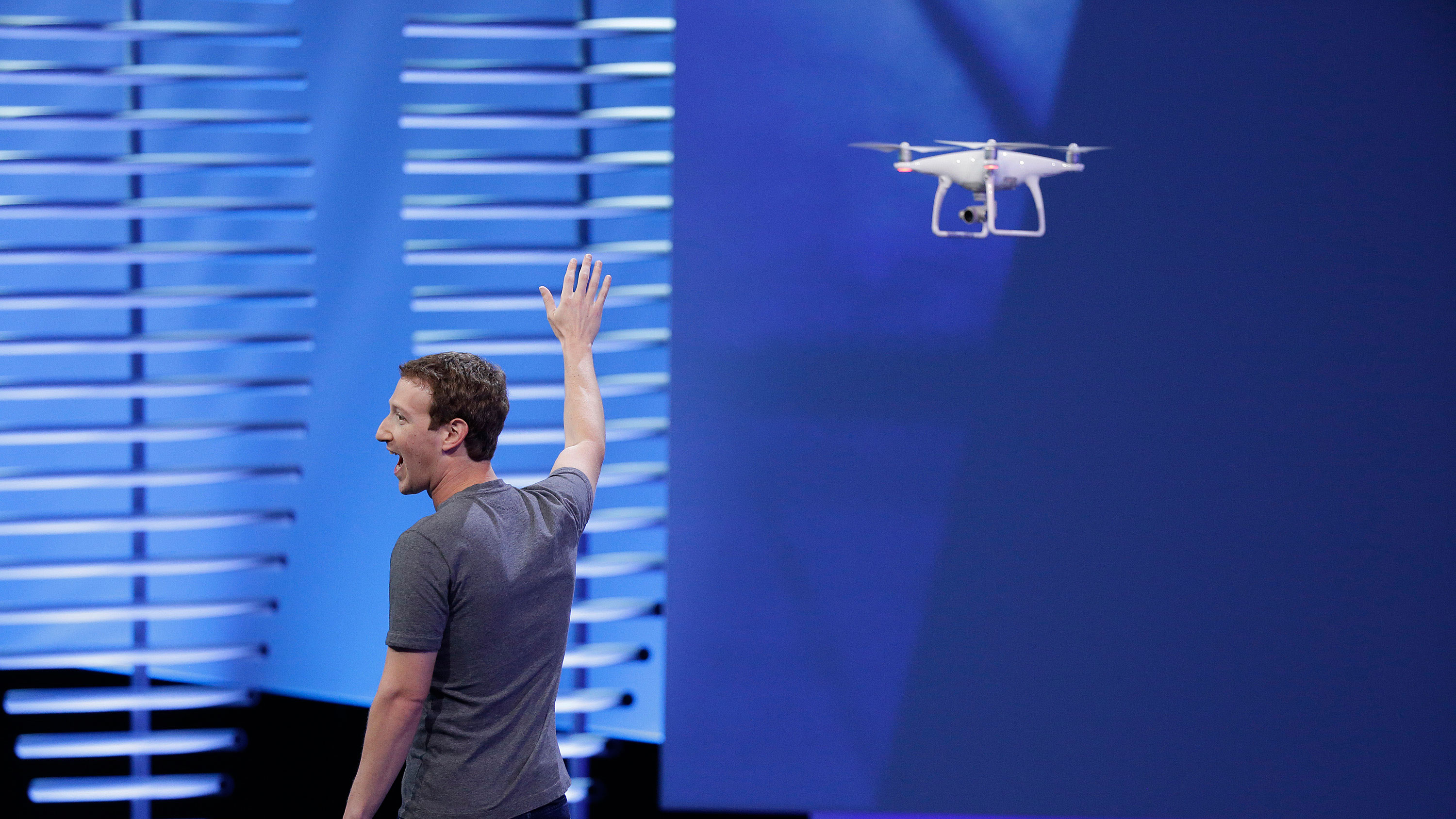 """Facebook CEO Mark Zuckerberg points to a drone flying behind him during his keynote address at the F8 Facebook Developer Conference Tuesday, April 12, 2016, in San Francisco. Facebook says people who use its Messenger chat service will soon be able to order flowers, request news articles and talk with businesses by sending them direct text messages. At its annual conference for software developers, Zuckerberg said the company is releasing new tools that businesses can use to build """"chat bots,"""" or programs that talk to customers in conversational language. (AP Photo/Eric Risberg)"""