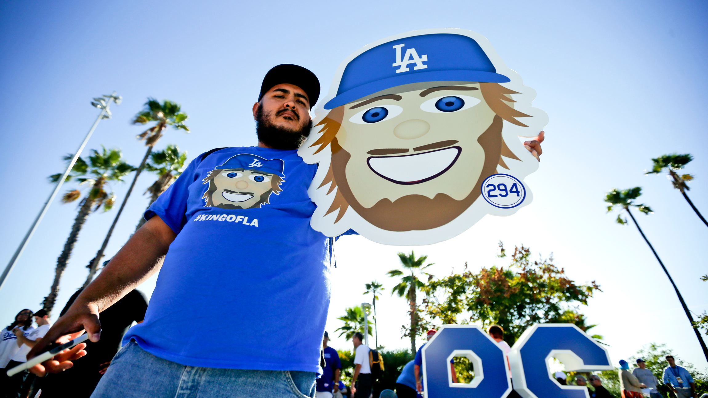 Miles Alcala holds up a emoji of Los Angeles Dodgers starting pitcher Clayton Kershaw before Game 1 of baseball's National League Division Series against the New York Mets, Friday, Oct. 9, 2015 in Los Angeles. (AP Photo/Gregory Bull)