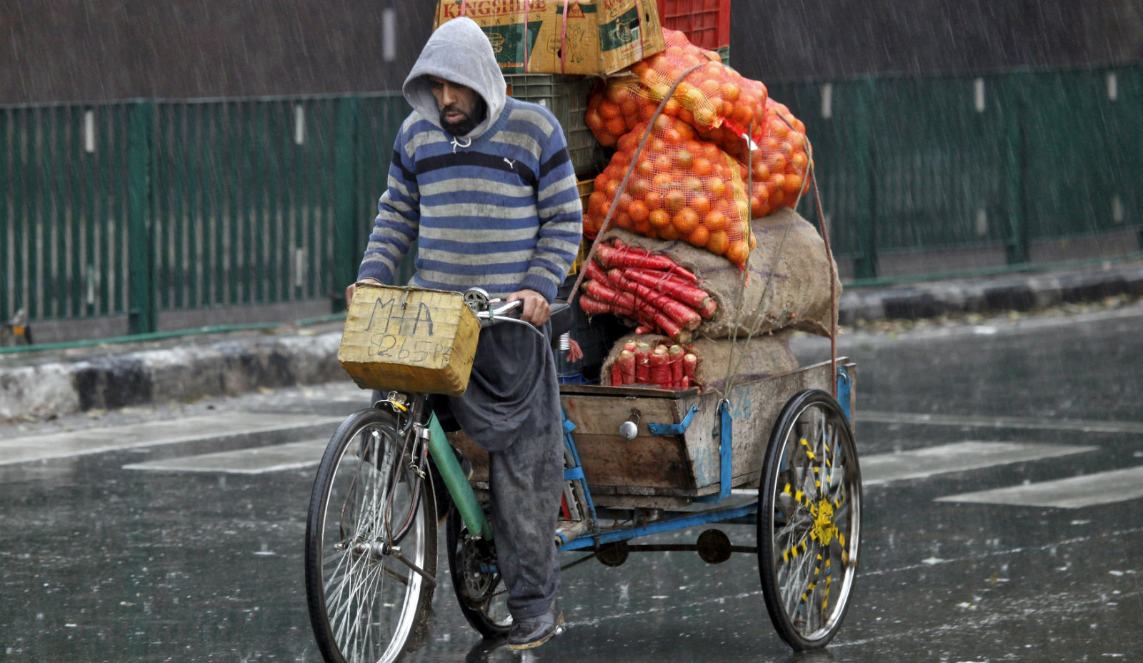 A man transports fruits and vegetables on a cycle rickshaw during a rain shower in Chandigarh, India, January 13, 2016. India's annual consumer price inflation edged up for a fifth consecutive month to 5.61 percent in December from a year earlier, matching analyst expectations on the back of rising food prices, government data showed on Tuesday.