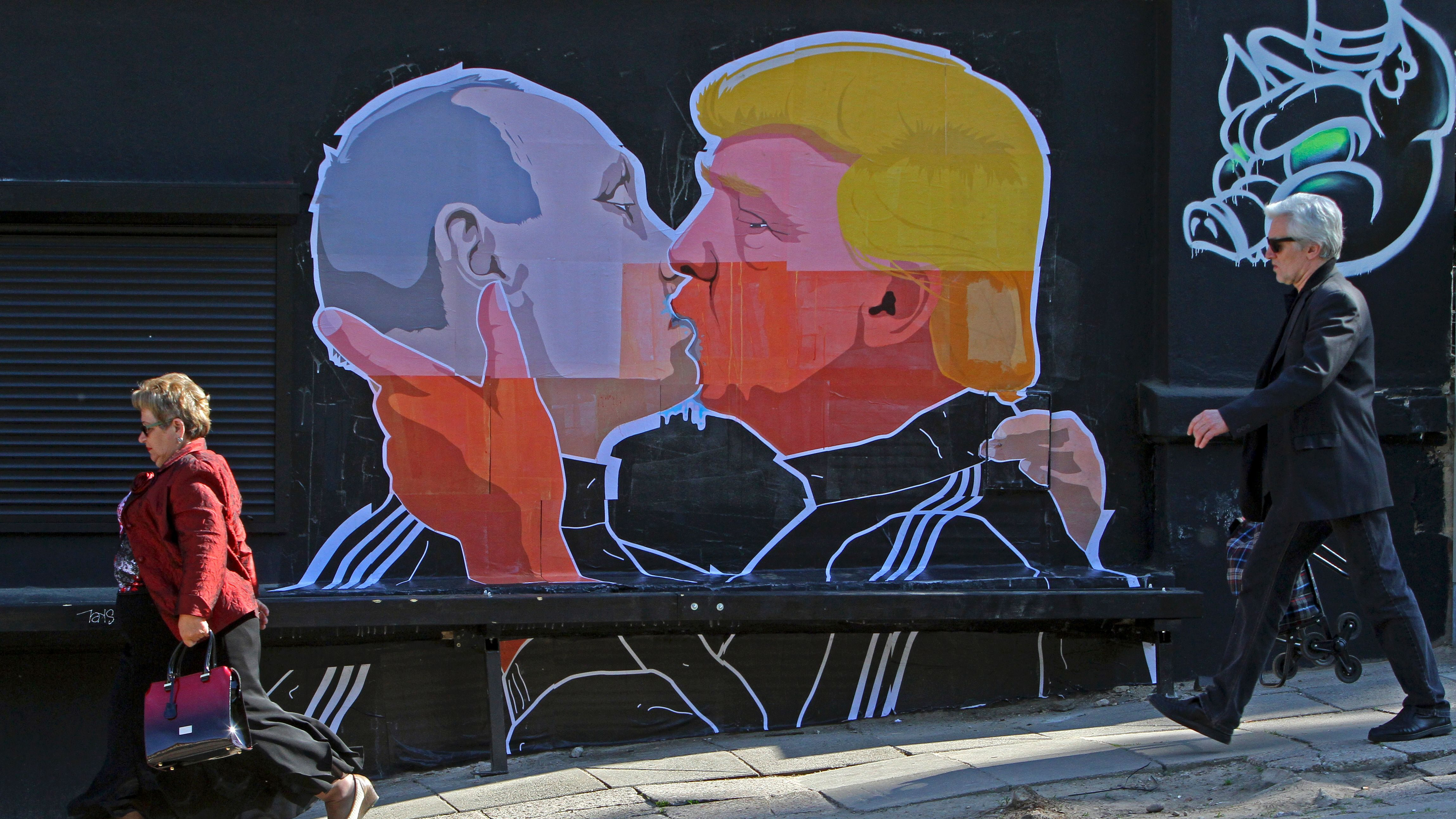 TOPSHOT - People walk past a mural on a restaurant wall depicting US  Presidential hopeful Donald Trump and Russian President Vladimir Putin greeting each other with a kiss in the Lithuanian capital Vilnius on May 13, 2016.