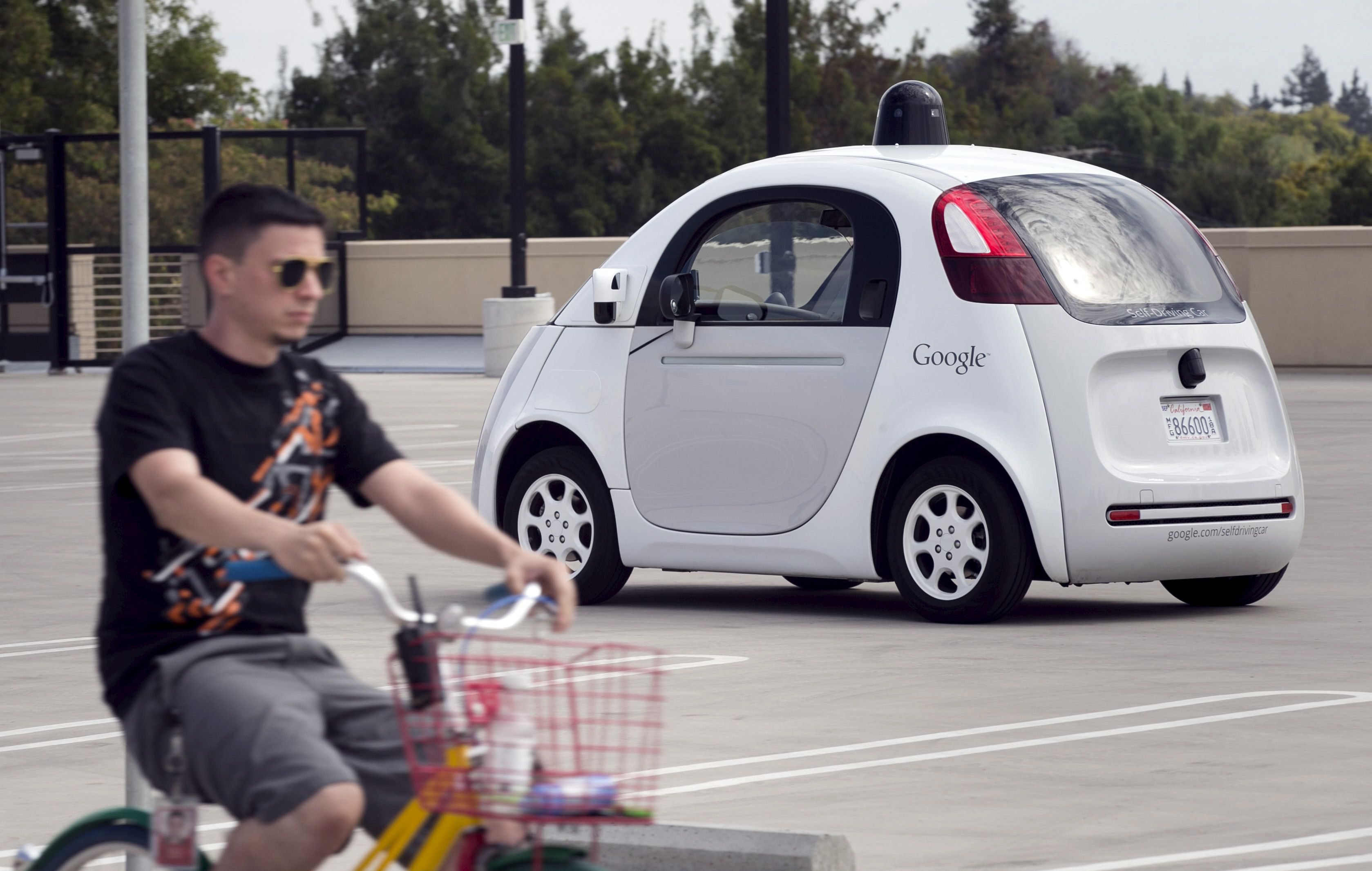 A Google employee on a bicycle acts as a real-life obstacle for a Google self-driving prototype car to react to during a media preview of Google's prototype autonomous vehicles in Mountain View, California September 29, 2015.  REUTERS/Elijah Nouvelage - RTS2BZN
