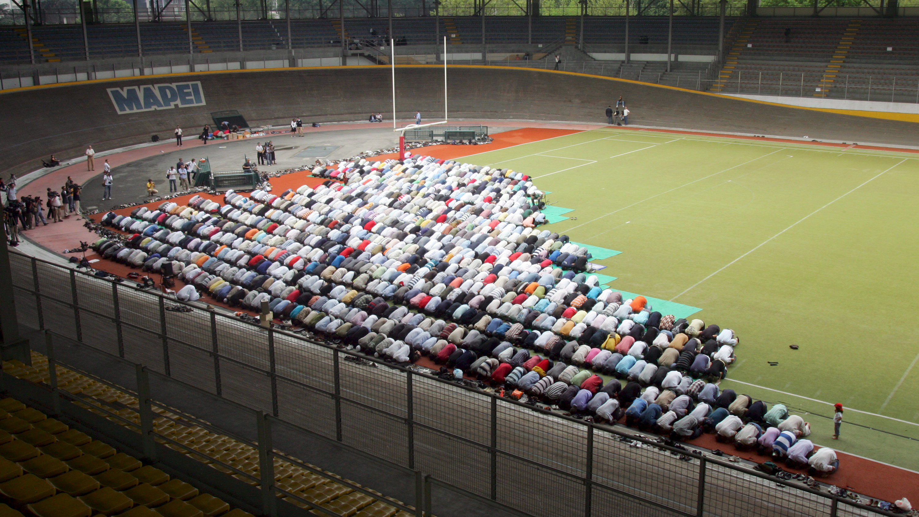 epa01417472 Members of the muslim community living in Milan pray during the Friday prayer held for the first time in Vigorelli velodrome, Italy, 18 July 2008 after the controversial mosque in viale Jenner was closed. EPA/MATTEO BAZZI