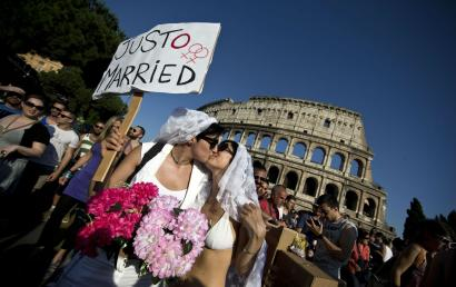 epa03746301 Two young women kiss as they take part in the annual Gay Pride parade near the Colosseum to protest against the discrimination of LGBT (Lesbian, Gay, Bisexual and Transgender) people in Rome, Italy, 15 June 2013. EPA/MASSIMO PERCOSSI