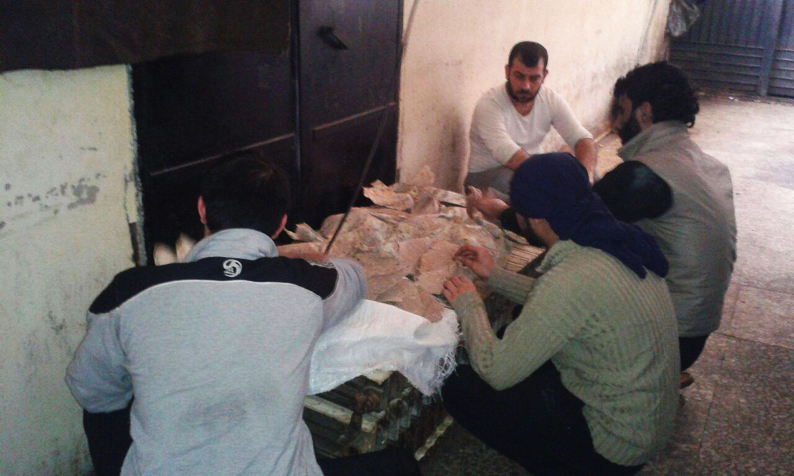Inmates in Hama Central Prison scrape mold off dry bread, after taking over the prison. Supplies are running low.