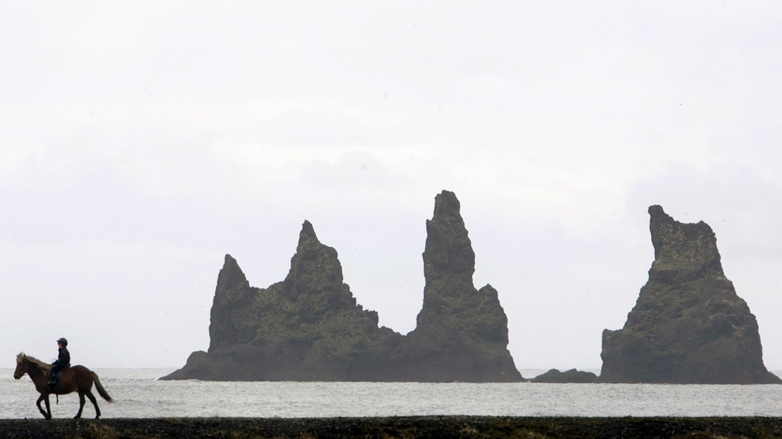 A horseback rider passes the Reynisdrangur rocks near the town of Vik on Iceland's southern coast May 10, 2008. REUTERS/Bob Strong (ICELAND) - RTX5K1F