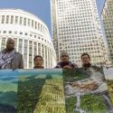Indigenous leaders hold pictures of deforested land.