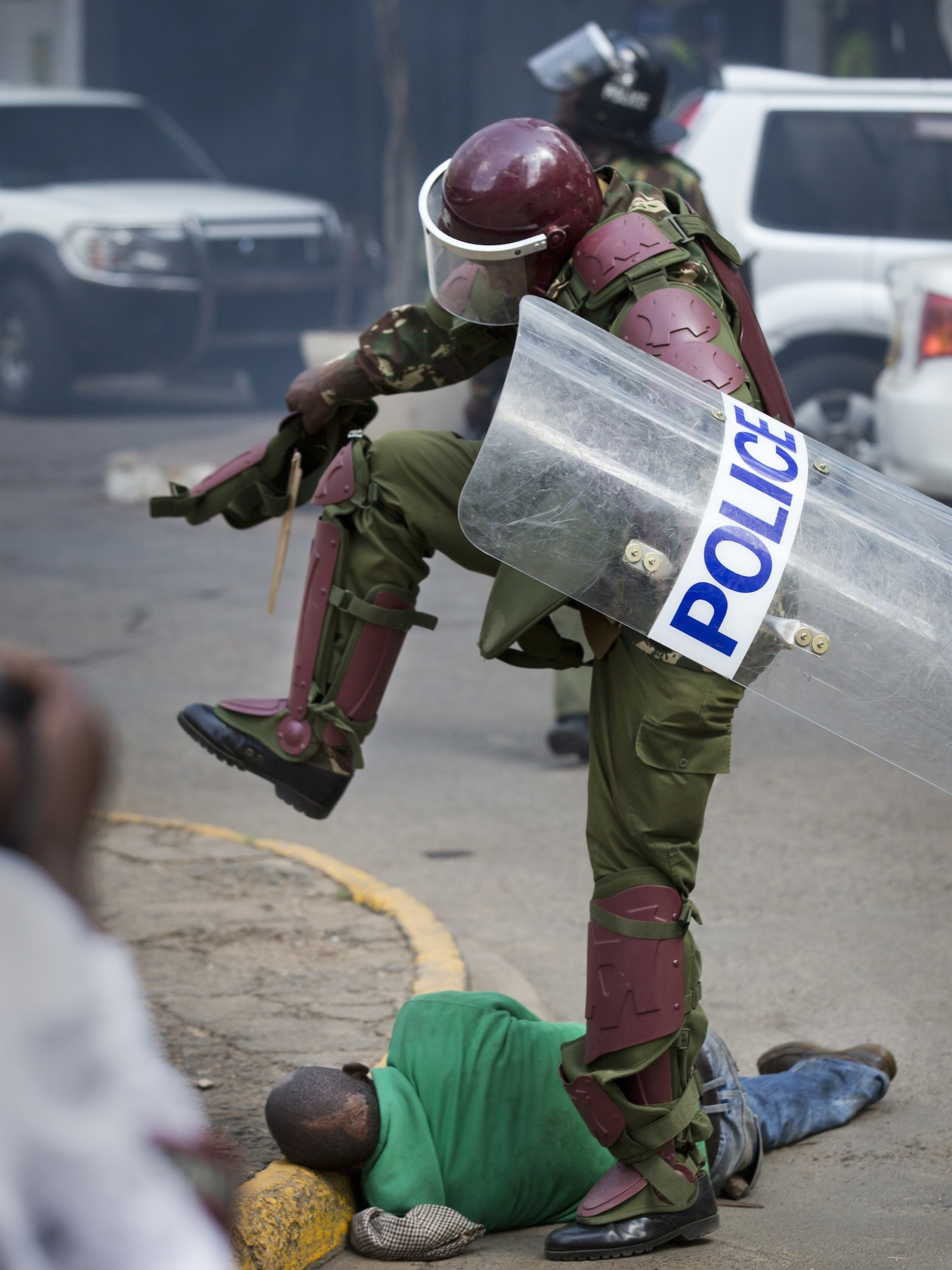 A Kenyan riot policeman repeatedly kicks a protester as he lies in the street.