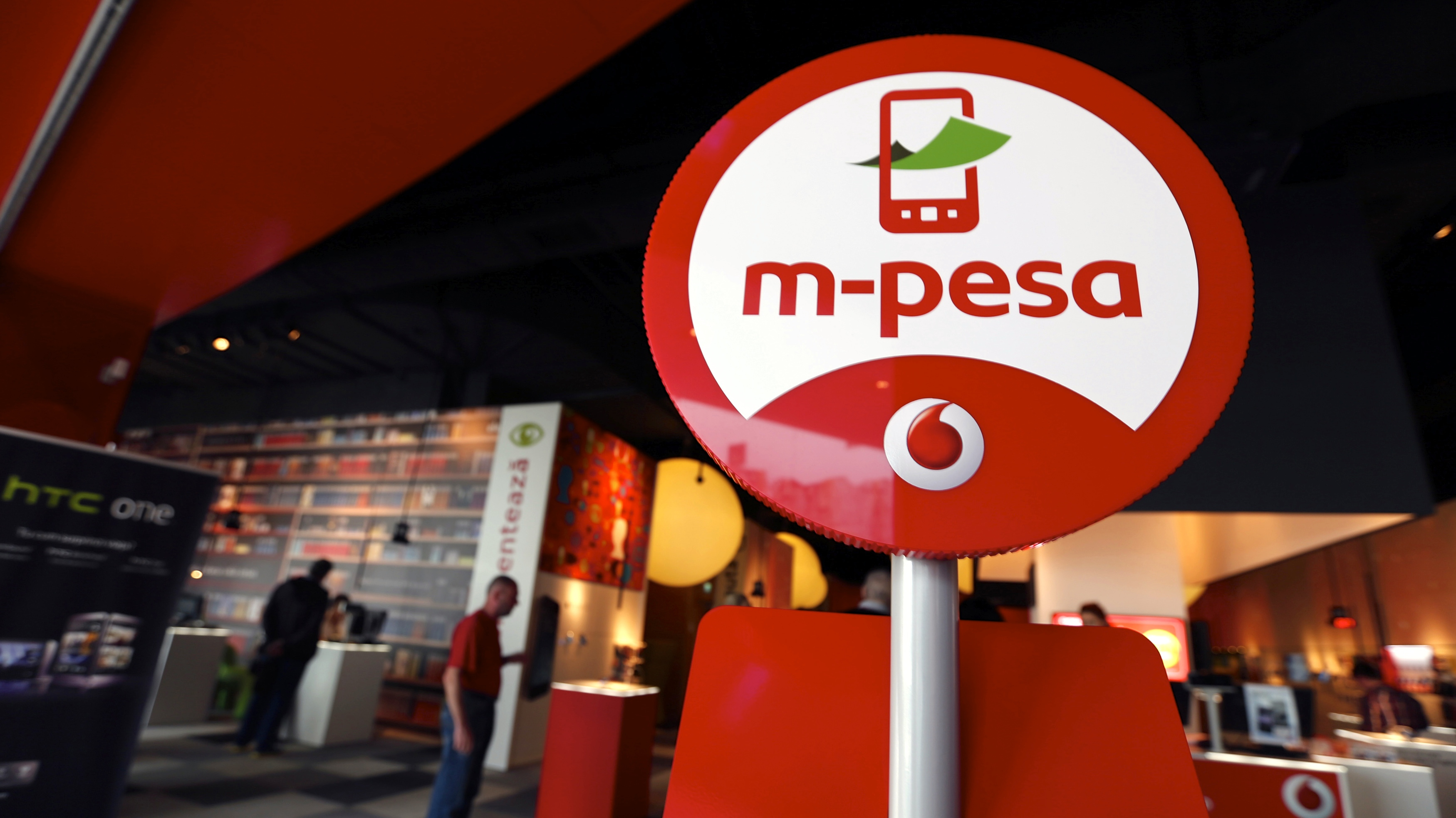 The logo of M-Pesa's text message transactions option for mobile phones is seen at a Vodafone shop in Bucharest April 1, 2014. Vodafone brought the mobile money service that has revolutionised banking in Africa to Romania on Monday, offering M-Pesa text-message transactions to millions of customers in its first push into Europe. Vodafone said it had chosen Romania to target the seven million people there who still mainly use cash rather than cards, and others with bank accounts who could still benefit from transferring money by text.