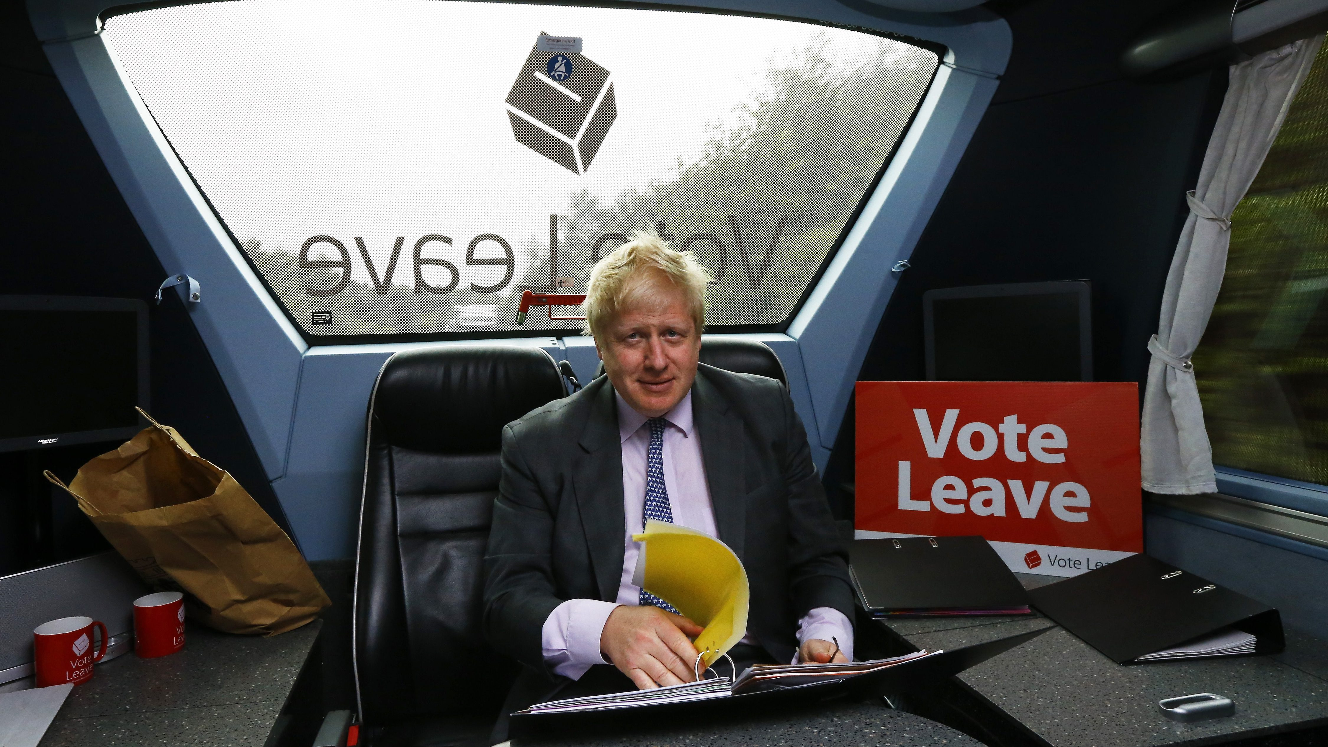 Former London Mayor Boris Johnson works in the back of the Vote Leave bus as it heads towards Exeter