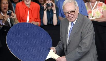 Berkshire Hathaway chairman Buffett plays table tennis with world champion Hsing using a giant paddle at the Berkshire Hathaway annual meeting weekend