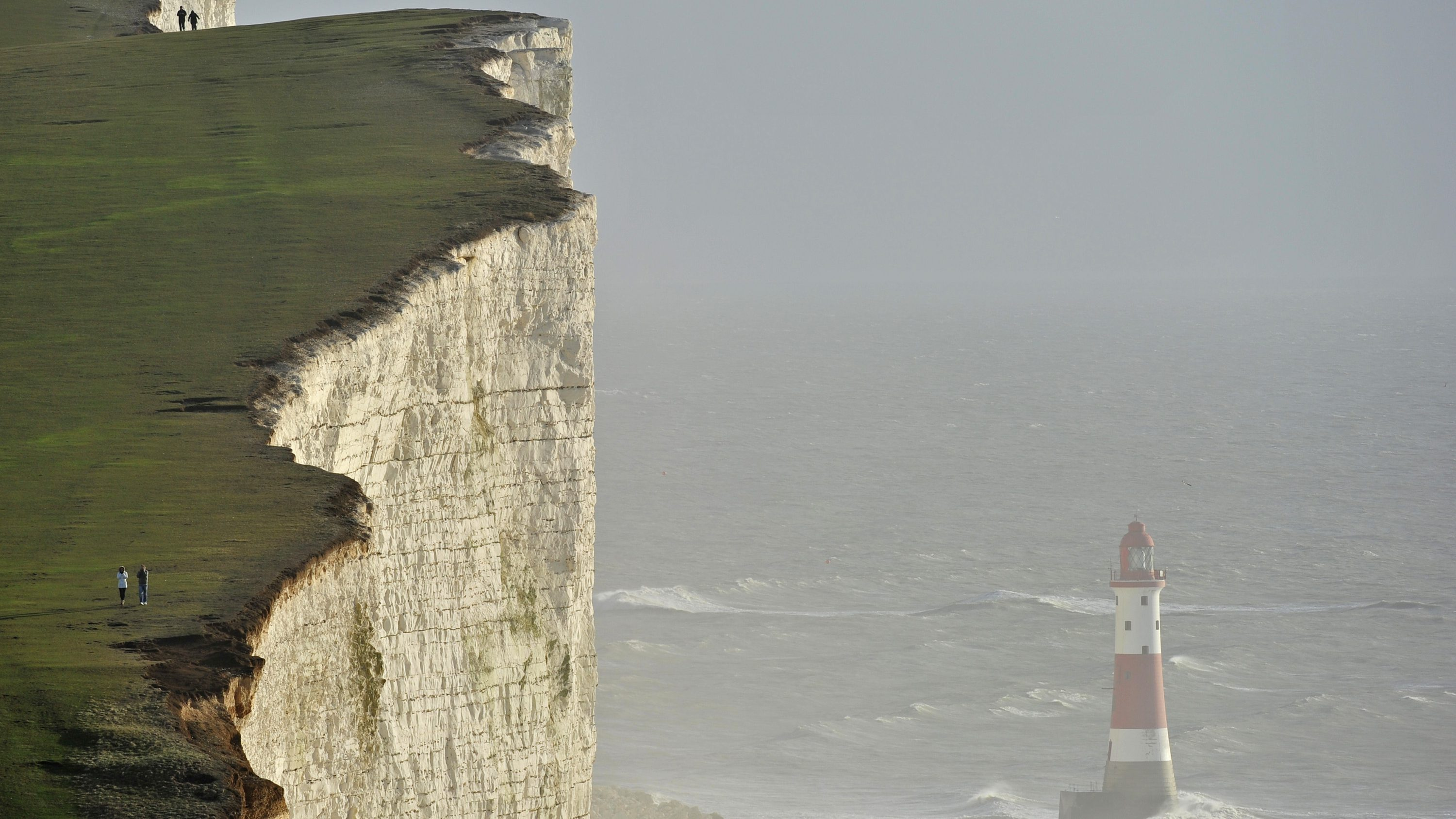 Walkers look out over Beachy Head lighthouse and heavy seas in the English Channel at Beachy Head in East Sussex in southern England