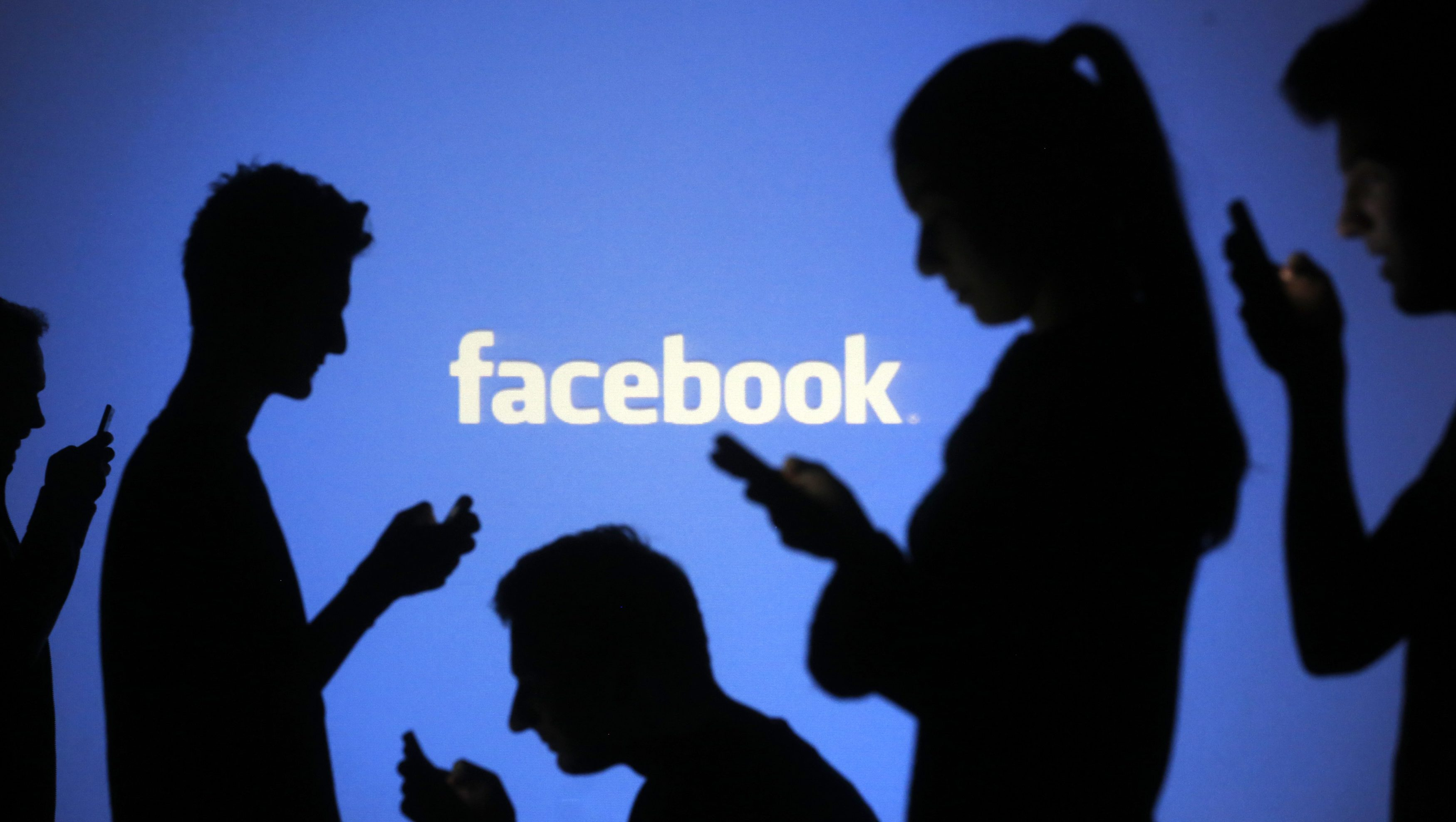People are silhouetted as they pose with mobile devices in front of a screen projected with a Facebook logo, in this picture illustration taken in Zenica October 29, 2014. Facebook Inc warned on Tuesday of a dramatic increase in spending in 2015 and projected a slowdown in revenue growth this quarter, slicing a tenth off its market value. Facebook shares fell 7.7 percent in premarket trading the day after the social network announced an increase in spending in 2015 and projected a slowdown in revenue growth this quarter.