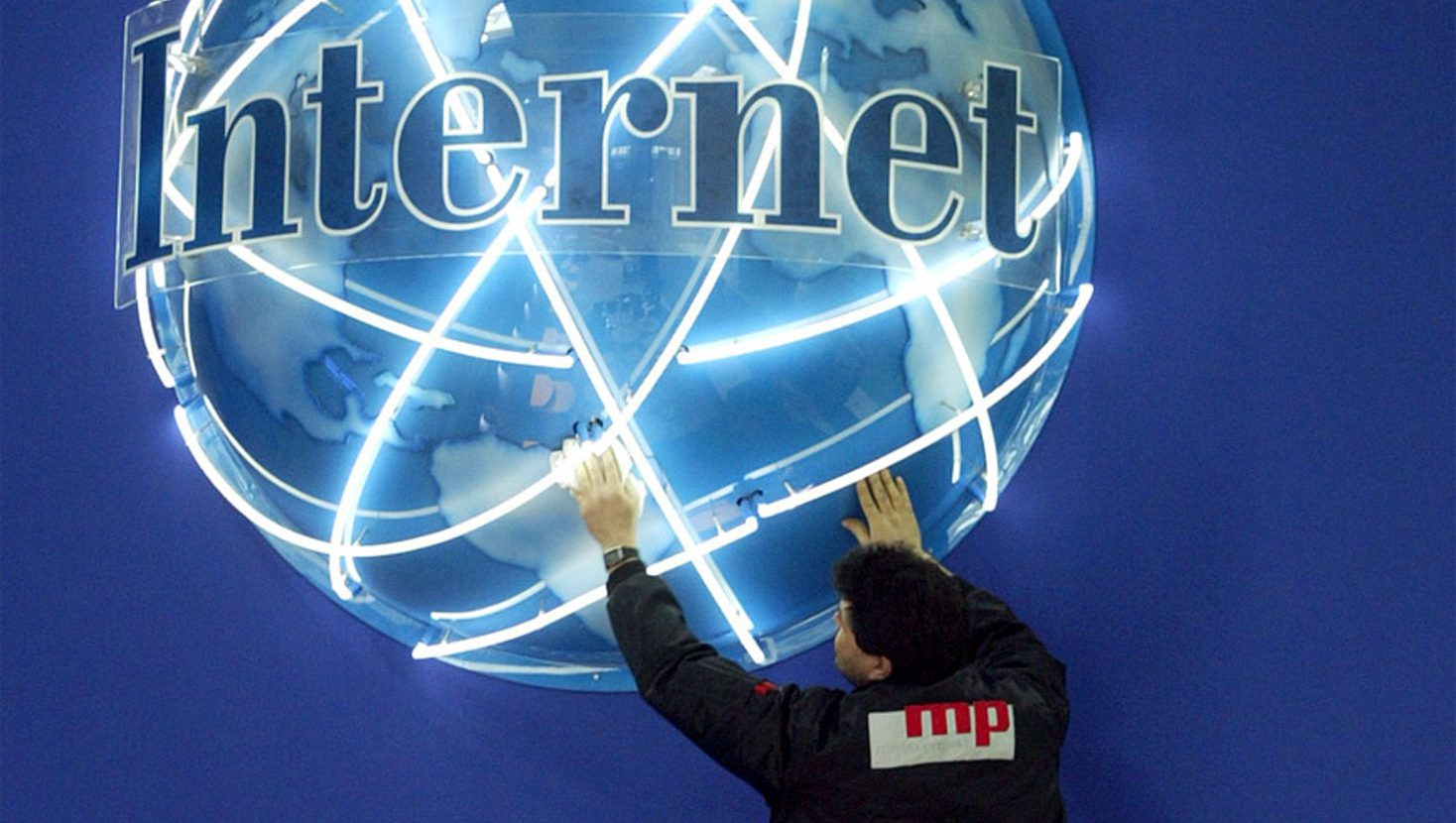 A worker adjusts a globe advertising internet connections in preparation for the world's largest computer fair, CeBIT, in Hanover March 15, 2004. Some 6,400 exhibitors from 64 nations present their latest products at the world's largest computer and information technology fair, CeBIT, which runs from March 18 until March 24, 2004.