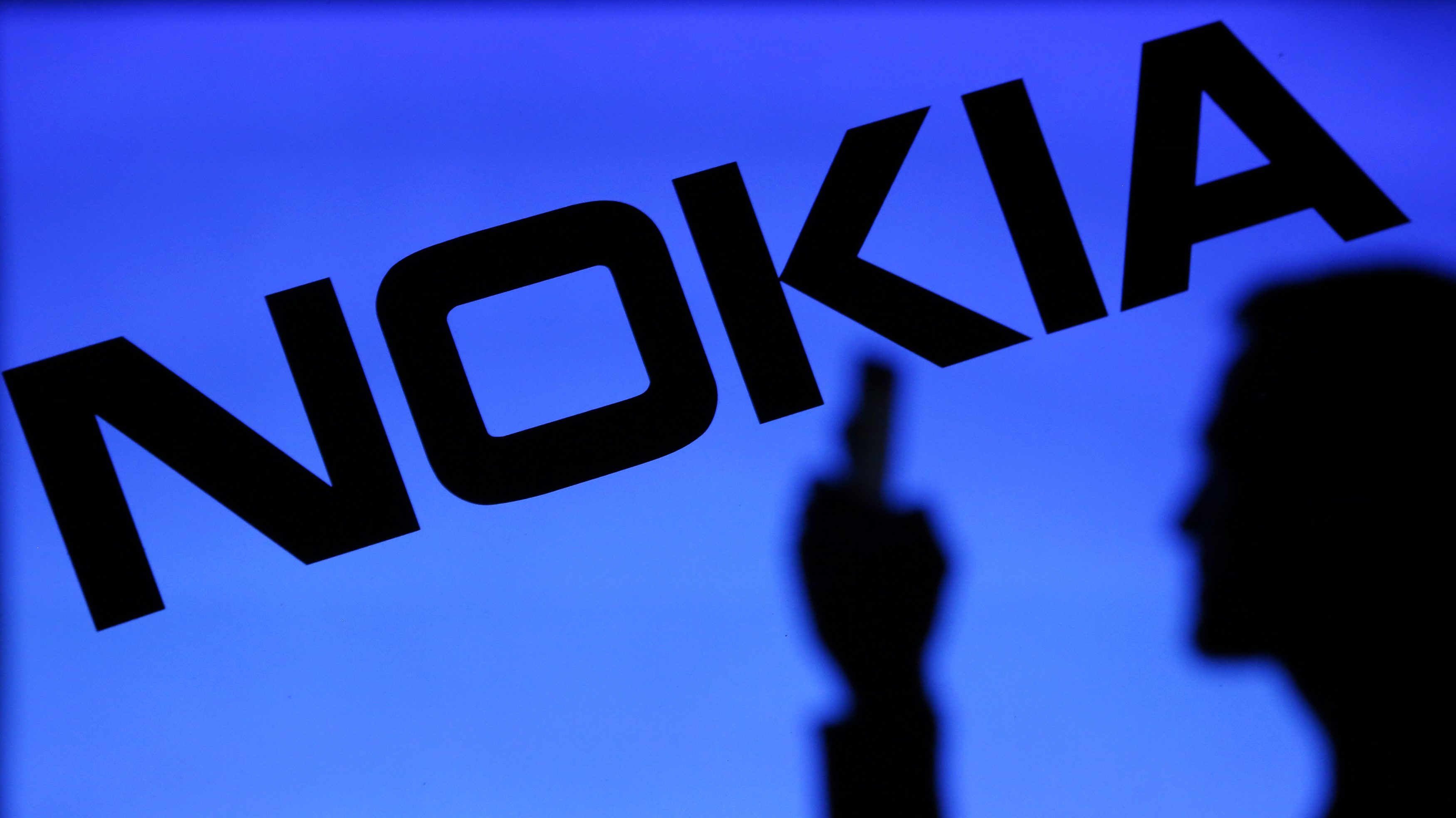 A Photo Illustration Of Man Silhouetted Against Nokia Logo