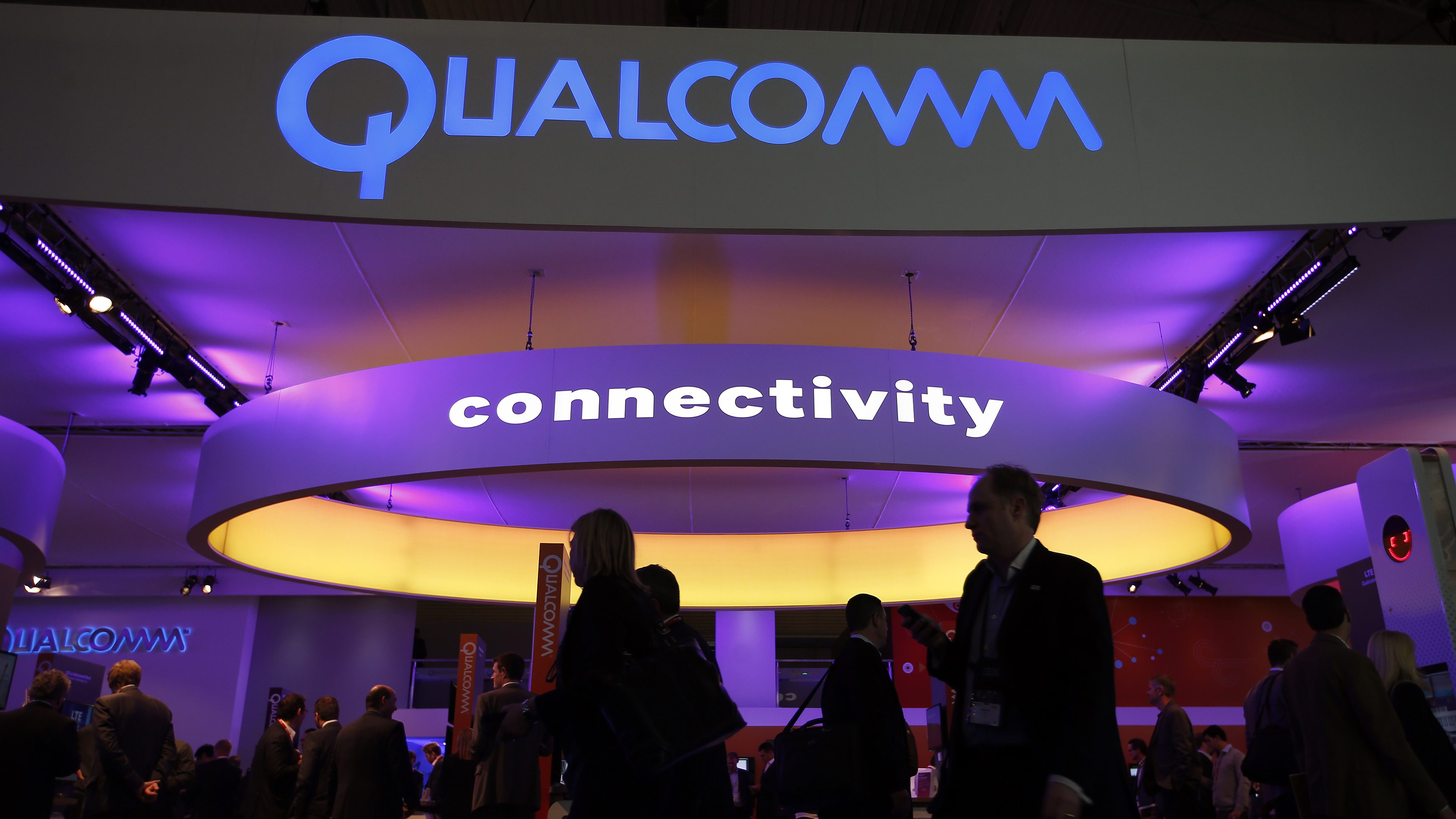 Visitors walk past the Qualcomm stand at the Mobile World Congress in Barcelona, February 24, 2014. The world's biggest mobile brands will jostle for the spotlight at the premier mobile industry event this week in Spain, but away from the glitzy displays chipmakers will be preoccupied with China, the largest mobile market on the planet.