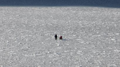 Two men are fishing on the ice in the Gulf of Finland in Tallinn