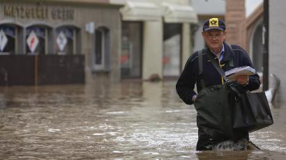 Postman Gerhard Beck wades through the flooded streets as he delivers letters and postcards in the old part of Wertheim, 100km south of Frankfurt