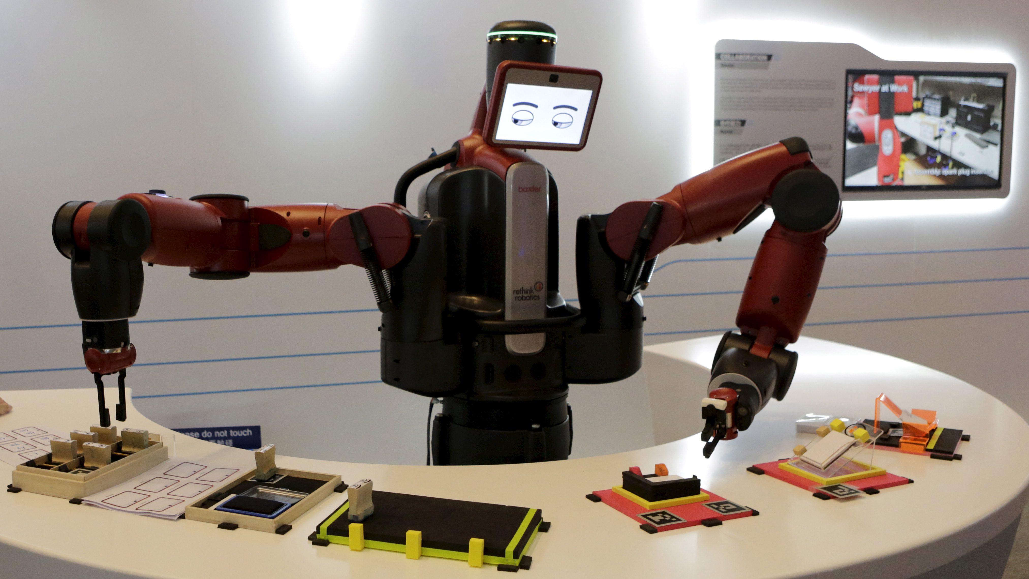 A Baxter robot of Rethink Robotics picks up a business card as it performs during a display at the World Economic Forum (WEF), in China's port city Dalian, Liaoning province, China, September 9, 2015. Chinese robotics firms are grappling with a weakening economy and slumping automotive sector, and industry insiders already predict a market bubble just three years after the central government issued policies to spur robotics development. Picture taken September 9, 2015.