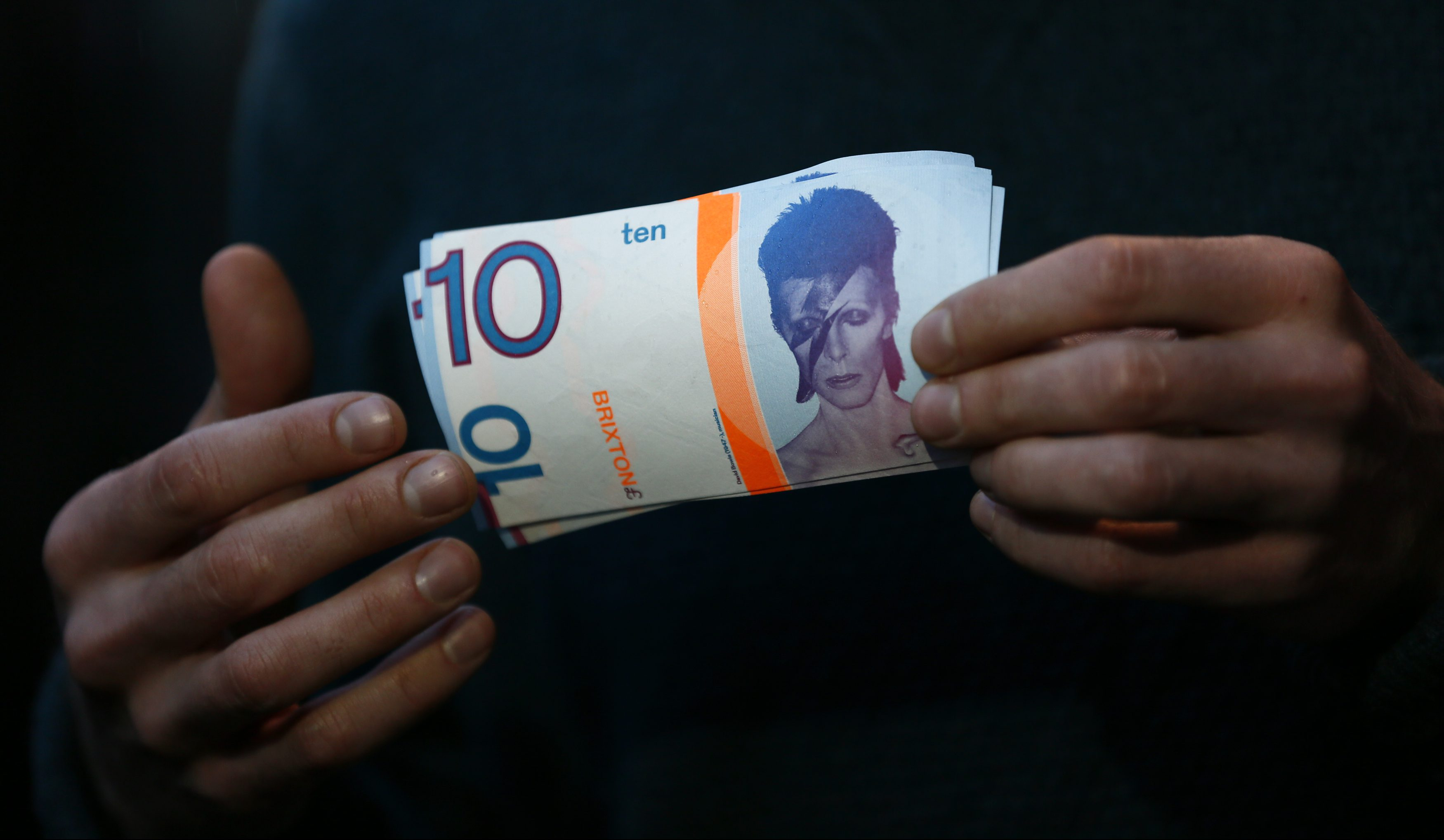 A man holds a 10 Brixton Pounds note, which is adorned with an image of Brixton native David Bowie in Brixton, south London