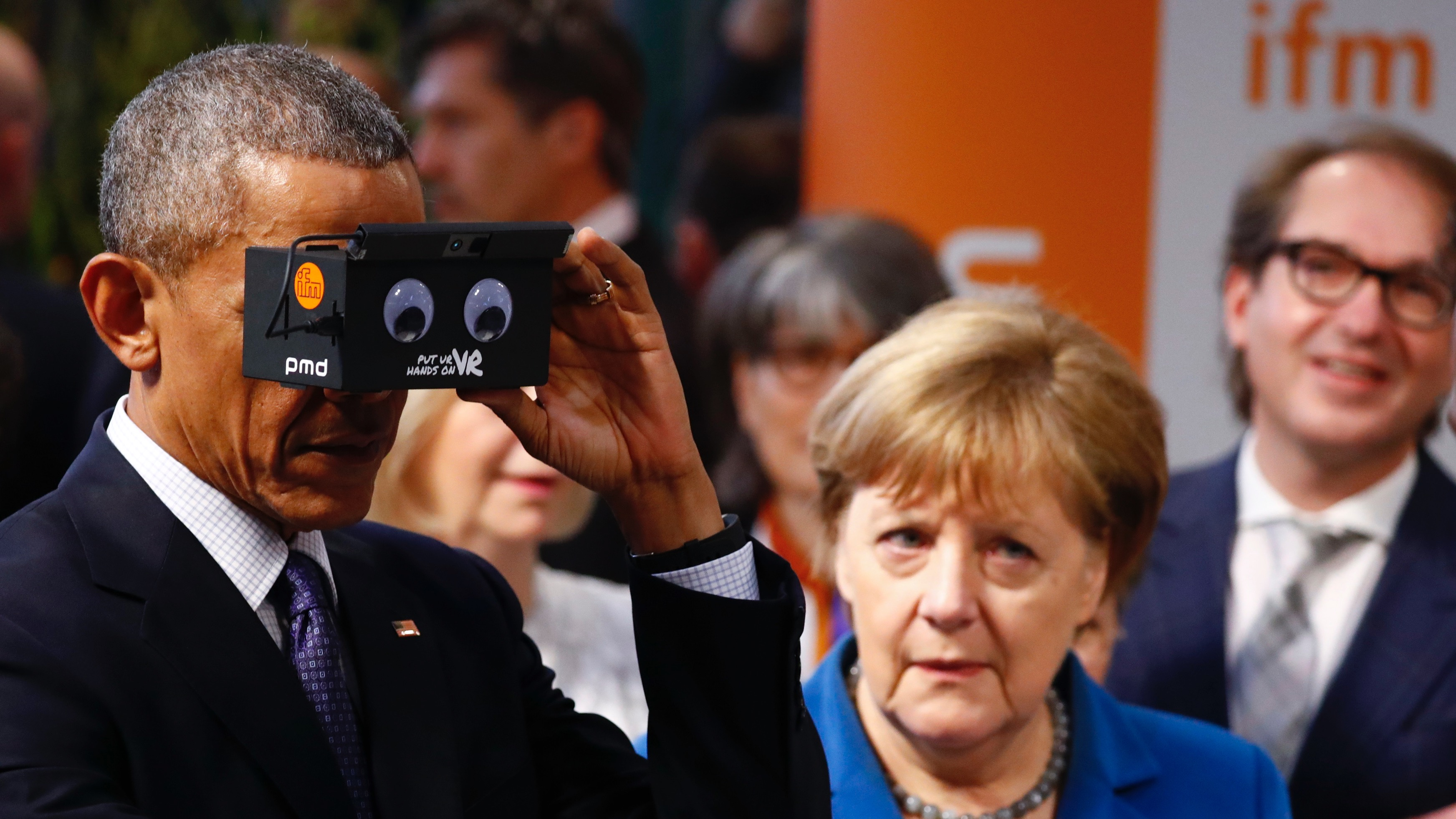 German Chancellor Angela Merkel stands with U.S. President Barack Obama as he tries the virtual reality device PMD during the opening tour of the Hannover Messe in Hanover, Germany April 25, 2016.      REUTERS/Kai Pfaffenbach - RTX2BHTS