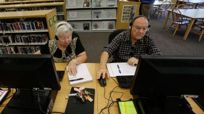 In this Wednesday, Sept. 10, 2014 photo, retirees Edna, left, and Pedro Cortes make use of computers at a branch of the Citrus County Library, in Beverly Hills, Fla. In Citrus County, more than a third of residents are senior citizens, the sixth-highest rate in the nation.(AP Photo/John Raoux)