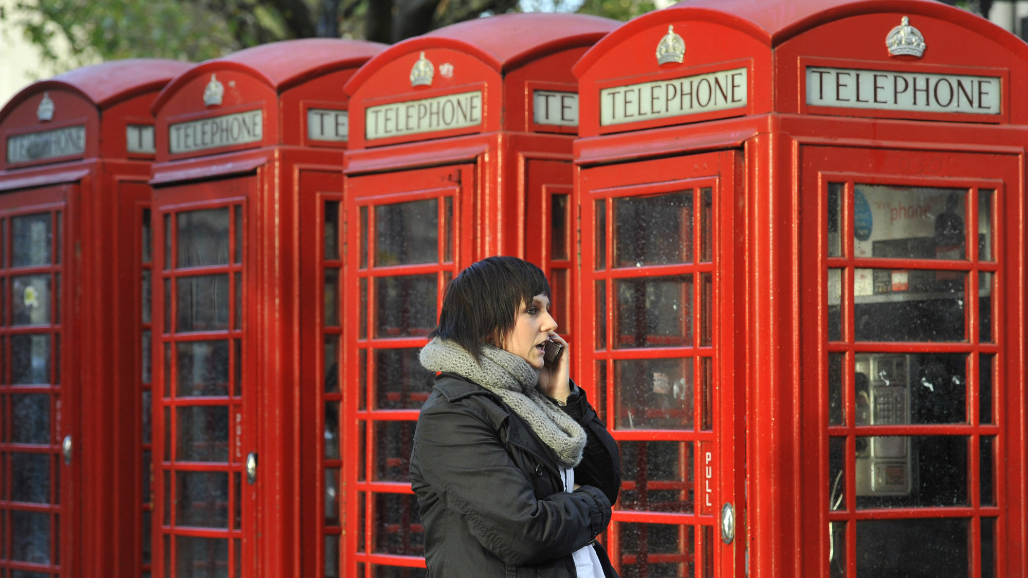 A woman speaks on her mobile phone outside a row of telephone boxes in central London November 11, 2010.