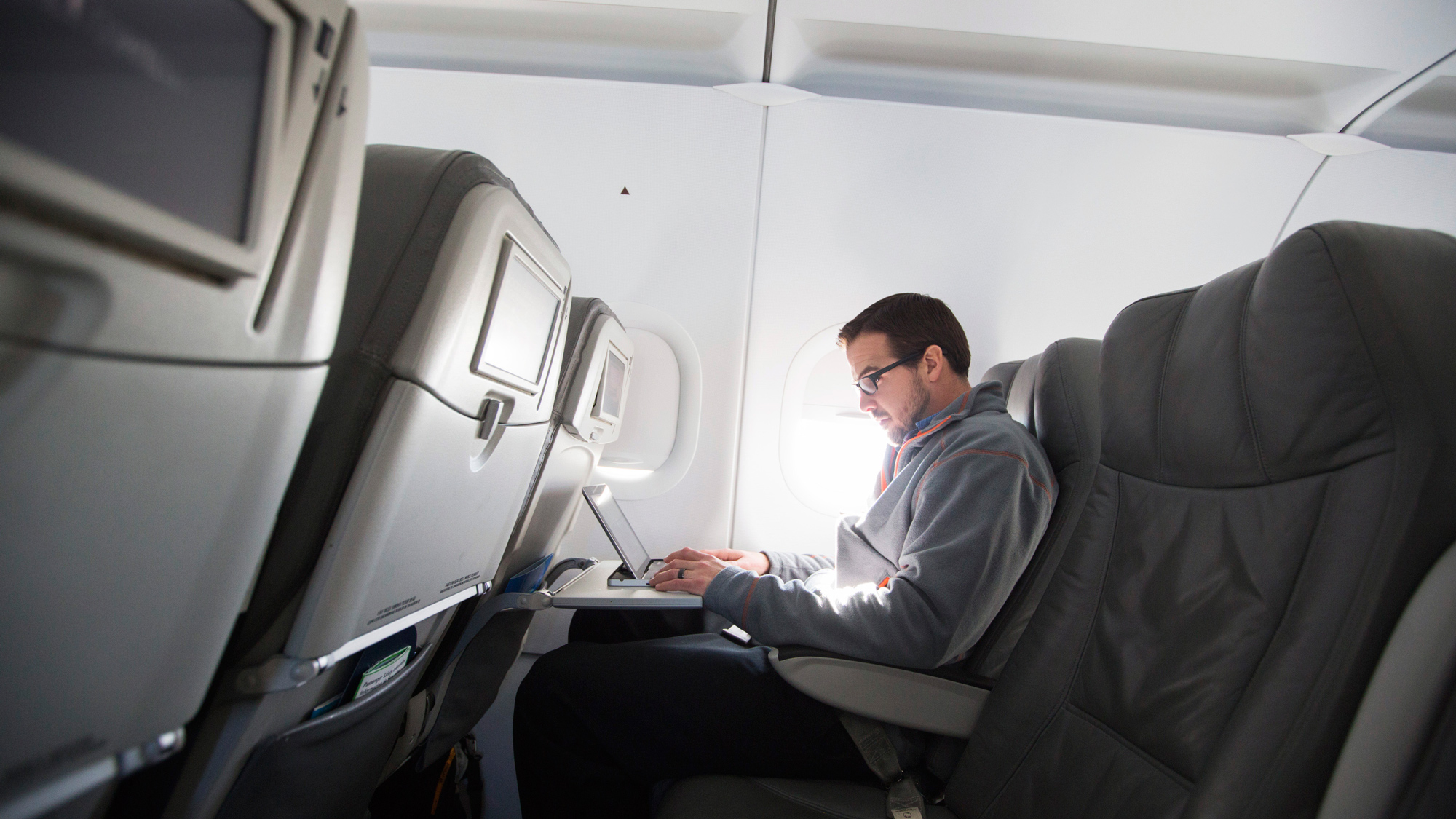 A man uses his laptop to test a new high speed inflight Internet service named Fli-Fi while on a special JetBlue media flight out of John F. Kennedy International Airport in New York December 11, 2013. Wi-Fi in the sky is taking off, promising much better connections for travelers and a bonanza for the companies that sell the systems. With satellite-based Wi-Fi, Internet speeds on jetliners are getting lightning fast. And airlines are finding that travelers expect connections in the air to rival those on the ground - and at lower cost. Picture taken December 11, 2013. To match Analysis AIRLINES-WIFI/ REUTERS/Lucas Jackson (UNITED STATES - Tags: TRANSPORT BUSINESS SCIENCE TECHNOLOGY TELECOMS TRAVEL)
