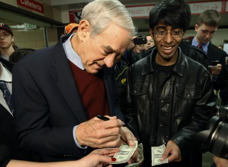Republican presidential candidate Rep. Ron Paul, R-Texas, signs an autograph on a dollar bill as he visits a caucus site Tuesday, Feb. 7, 2012, in Coon Rapids, Minn. (AP Photo/Charles Rex Arbogast